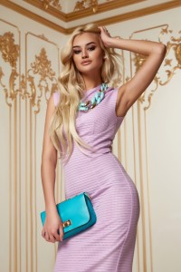 Beautiful young sexy blond girl with long curly hair with a bright evening make-up, wearing a slinky silk pink dress high heels a little blue bag necklace, wealth and luxury, party background baroque.