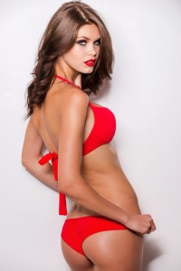 Proud of her perfect body. Rear view of attractive young brown hair woman in red bikini posing against white background