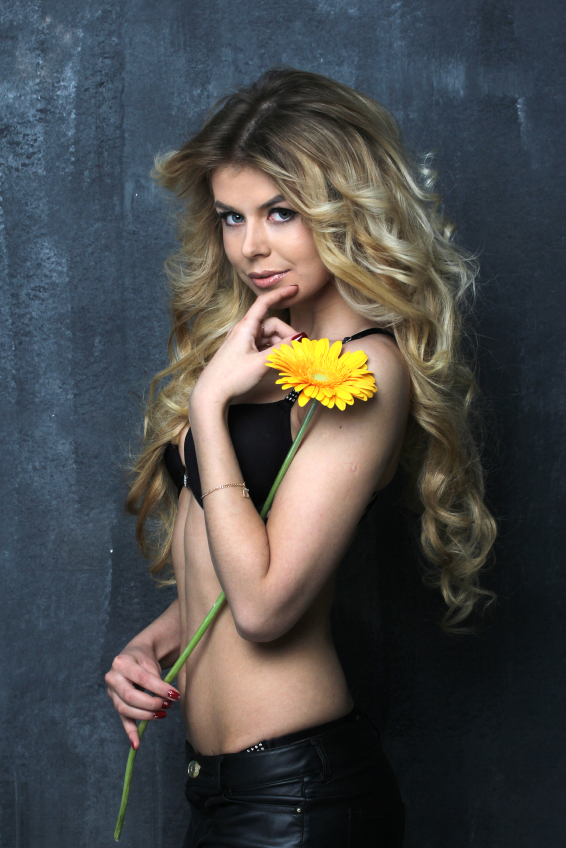 Portrait of beautiful blond girl with red gerbera in black underwear. On blue wall background