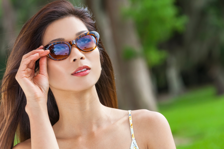 Outdoor portrait of a beautiful young Chinese Asian young woman or girl wearing sunglasses